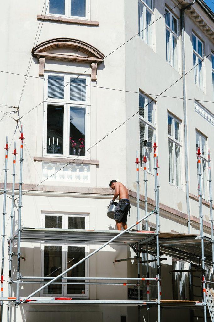 homme torse nu qui travaille sur un échafaudage